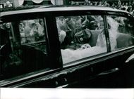 Prince Edward, Duke of Kent and wife Katharine, Duchess of Kent waving to people from the inside of their car on their wedding day.  - Jun 1961
