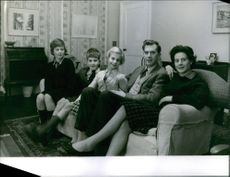 """A family sitting on a couch for a photo.  """"Ryle""""  1961"""