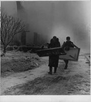 Scene of the horrible effects of total war in Finland, two men carrying table. 1940