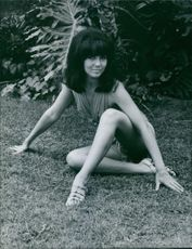 In the picture: one of those ravishing beauties: Rachel Roman, sitting on a grassy field.