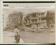 woman look at the destroyed roofs and trees