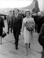 Princess Alexandra, holding a bouquet of flowers, with Angus Ogilvy, walking in the airport with some leaders and officials.