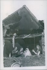 1945 Wedding reception held in a bombed house. The Bride and Bridegroom being toasted by an R.A.F. officer and a bridesmaid.