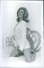Caron Gardner striking a pose on the bed for a photograph.