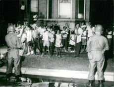 Black children on the side of the street guarded by military men in Ohio.  Taken - 25 July 1966