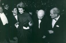 A photo of Austrian American film director Otto Preminger and wife Hope Preminger with Georges Cravenne arrived at the party. 1963.