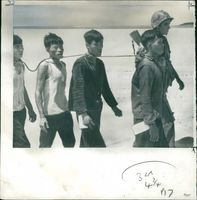 Viet Cong suspects tied together by a rope at their necks during Vietnam War