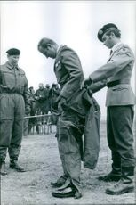 A soldier helping Juan Carlos de Bourbon to put on the outfit.