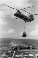 A helicopter with a hanging cargo over a carrier ship