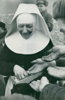 Nun smiling as she give cigarettes to German soldiers prisoners. - 1949