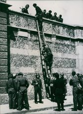Soldiers climbing over the house.