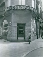 A view of a bank, woman walking on sidewalk.