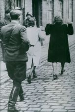 1945 Danish women who socialized with Germans are being escorted away by an armed freedom fighter.