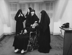 Nuns looking at a man dressed as a nun in a movie scene.