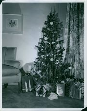 Christmas tree and gifts in the corner of the room.