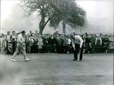 Two men playing golf and other people watching them.