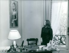Woman standing and looking at her own portrait.