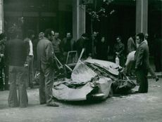 People looking at the smashed car.
