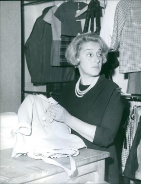A woman holding a young child's coat at a counter.