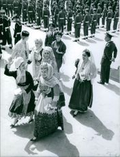 Juan Carlos walking with people, few of them wearing traditional clothing.