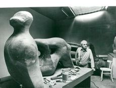 """Sculptor Henry Moore in his studio with his sculpture """"Reclining Figure; Holes"""""""