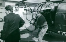 A patient being carried by three people from helicopter.