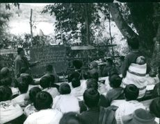1967  A photo of a man teaching the people of village. A supplementary education course for grown-ups held in a liberated Xieng Khoang.