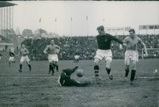 Footballers playing football in the ground while an athlete fell off.