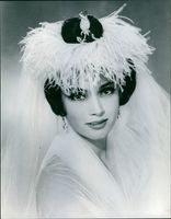 Marie-Hélène Arnaud wearing a bridal gown while posing for the camera.