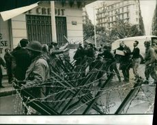 Rallying people receive baguettes in Algeria.  Taken - Mar. 1962