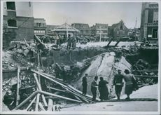 People gathered in street and looking at the ruins of building.