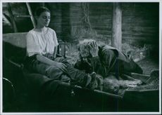 """In the film """"Ingen mans kvinna"""" (eng:No man's woman), Lissi Alandh sitting on a bed of hay while Max von Sydow kneels and leans on the bedside looking exasperated, 1953."""