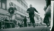 Pancake racers flipping to the finish to the amusement of shoppers in Yarmouth Market Place.