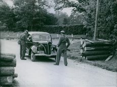 Troops holding up a car for questioning, while they being covered by sharpshooters behind barricades at the roadside, on a road in Southern England. 1940
