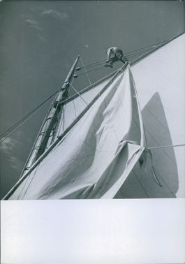 Man climbing over the rope of ships' mast. 1941
