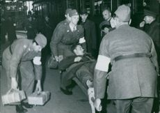 Ma Imo October 18 1943. Stone Berge. The prisoners of war in Trelleborg. Swedish Medic stow invalids on trainload. Soldiers holding and taking away a wounded by stretcher.