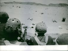 Soldiers looking at the dead bodies lying on the desert. 1967.