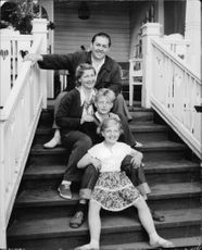 "Johan Jonatan ""Jussi"" Björling sitting on stair with his family and posing for picture."
