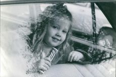 Princess Alexia of Greece and Denmark with a candy on her hand, pictured inside a vehicle.