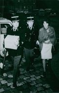 Two policemen walking with a woman at night.