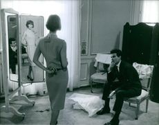 Horst Werner Buchholz sitting and looking a woman, posing in front of mirror.