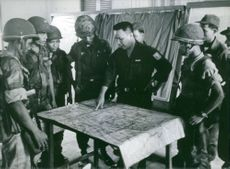 A leader guiding the soldiers and reading a map.