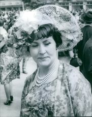 A woman wearing a hat adorned with flowers.