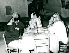 Princess Soraya and another people dining and talking outside.