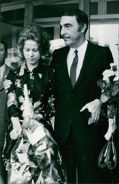 Man and woman standing, holding flowers and looking down.