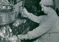 Apotekarnes Mineralvattenfabrik. Mrs. Brita Larsson at a tapping machine