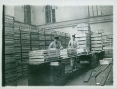 Two participants at field operation are packing pallets.