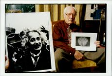 Dr. Thomas Harvey with a photo of Dr. Albert Einstein's brain. The portrait picture of Einstein was taken around 1930.