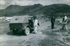 Man standing outside his jeep and looking at guards.