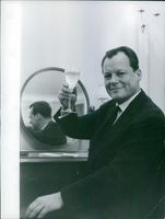 Willy Brandt toasting his drink.